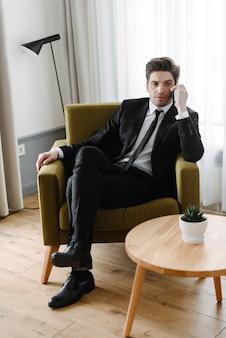 Foto van een denkende knappe zakenman in een zwart pak die op zijn mobiel praat terwijl hij op een fauteuil in een hotelappartement zit