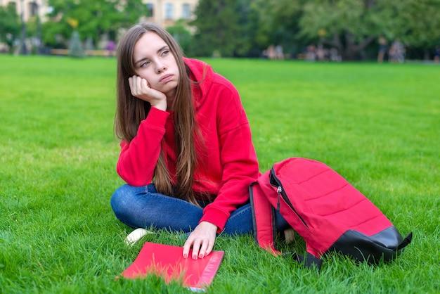 Foto van een depressief, passief, verdrietig tienermeisje dat op een groen grasveld zit, is niet bereid om een thuistaak te doen die wegkijkt, leunend op de hand