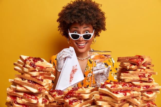 Foto van een donkere vrouw die netjes en goed gekleed is, poses met cocktailglas en servet, stijlvolle kleding draagt, vrije tijd doorbrengt in een luxe restaurant, heerlijke jam toast op voorgrond