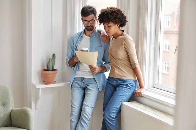 Foto van een donkere vrouw en haar man denken hoe schulden te voldoen, kijk naar rekeningen bij het raam