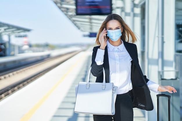 Foto van een elegante vrouw met een beschermingsmasker die met tas en koffer in het treinstation loopt