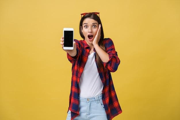Foto van een emotioneel geschokte jonge mooie vrouw die geïsoleerd staat over een gele achtergrond met behulp van een mobiele telefoon die opzij kijkt.