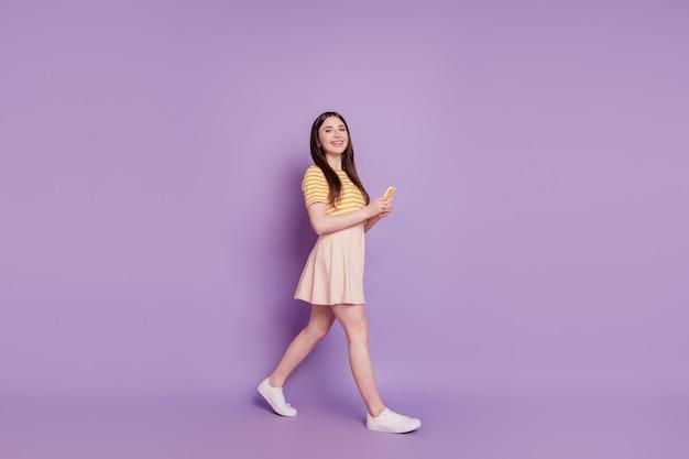 Foto van een energetisch positief charmant schattig meisje dat aan de telefoon loopt te chatten op een paarse achtergrond