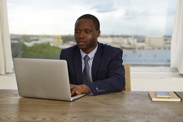 Foto van een ernstige geconcentreerde kantoormedewerker met een donkere huidskleur in formele kleding die een drukke, gerichte blik heeft, een generieke laptop gebruikt voor het werk, e-mail controleert of een rapport maakt. mensen baan en technologie