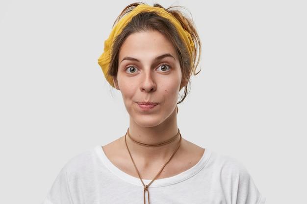 Foto van een europese vrouw met een aantrekkelijk uiterlijk, portemonnees lippen, heeft een gezonde, zachte huid, draagt gele hoofdband, casual t-shirt