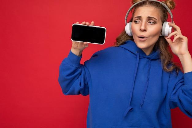 Foto van een fascinerende, blij geschokte jonge vrouw die een stijlvolle blauwe hoodie draagt, geïsoleerd over rood