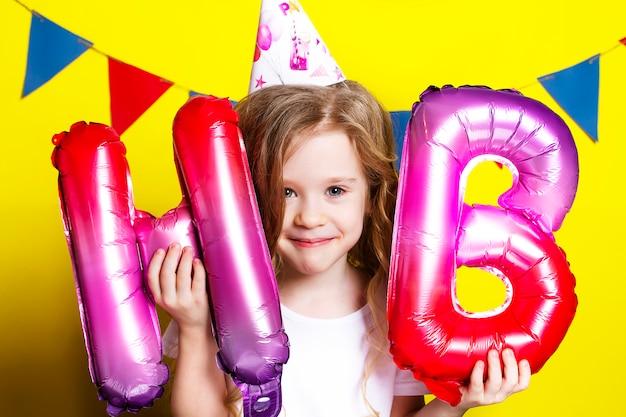 Foto van een feestvarken met ballonnen op een geel.