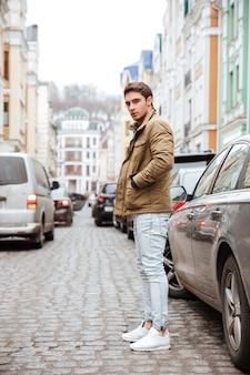 Foto van een geconcentreerde jonge man die op straat loopt en naar de camera kijkt.