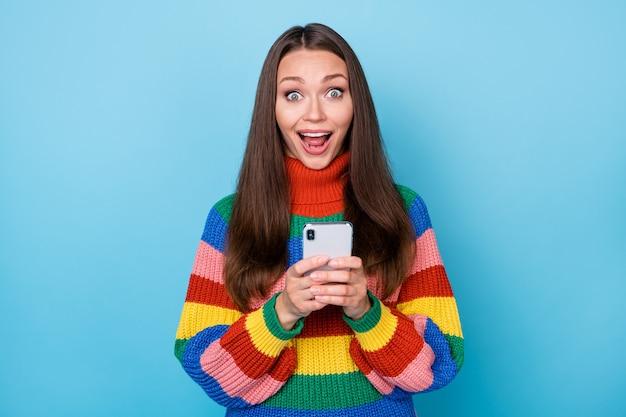 Foto van een gek verbaasd meisje dat smartphone-verslaafde blogs gebruikt, onder de indruk is van feedback op het sociale netwerk, een trui in regenboogstijl draagt, geïsoleerd op een blauwe achtergrond