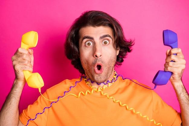 Foto van een gekke jongeman die met open mond staart en twee telefoons vasthoudt, een draad om de nek draagt, een oranje t-shirt geïsoleerd roze kleur achtergrond