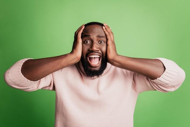 Foto van een gekke woedende geïrriteerde man die zijn oren dicht schreeuwt en een wit overhemd draagt over een groene achtergrond