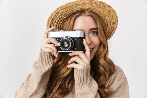 Foto van een gelukkig blij schattig jong tienermeisje poseren geïsoleerd over witte muur muur met camera fotograferen.