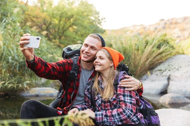 Foto van een gelukkig jong liefdevol stel buiten in een gratis alternatieve vakantiecamping boven de bergen, neem selfie via de mobiele telefoon.