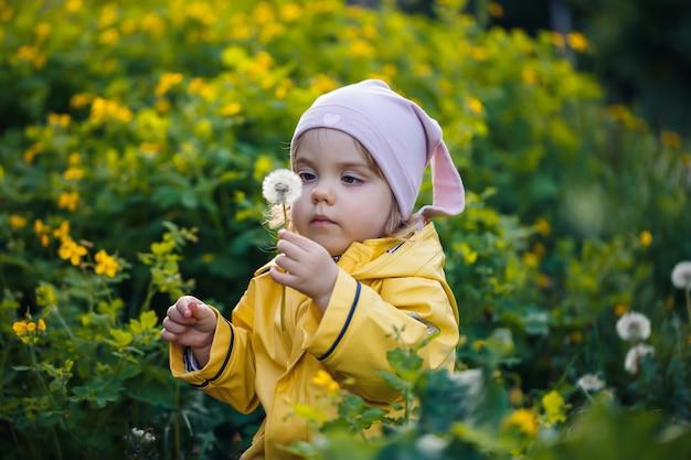 Foto van een gelukkig kindmeisje met een gele jas en witte hoed die in een weide speelt, bloemen omringd door een kind en gras, spelend in het veld tijdens zonsondergang. jeugd concept.