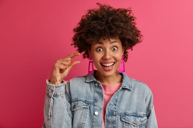 Foto van een gelukkig lachende vrouw toont een kleine hoeveelheid van iets, vormt de kleine afmeting van iets, heeft een opgewekte stemming, meet een klein onzichtbaar object, draagt spijkerbroeken, modellen en gebaren binnen