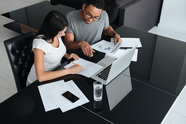 Foto van een gelukkig liefdevol jong stel dat laptop gebruikt en hun financiën analyseert met documenten. kijk naar papieren.