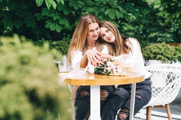 Foto van een gelukkig meisje dat op de schouder van haar moeder ligt en naar de camera kijkt