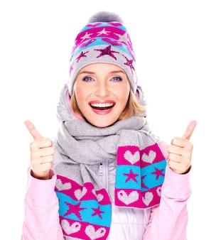 Foto van een gelukkig volwassen meisje in winterkleren met heldere positieve emoties toont duimen omhoog teken geïsoleerd op wit
