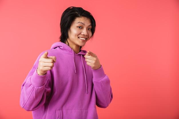 Foto van een gelukkige aziatische man die een sweatshirt draagt dat zich verheugt en met zijn vingers naar de camera wijst die over de rode muur is geïsoleerd