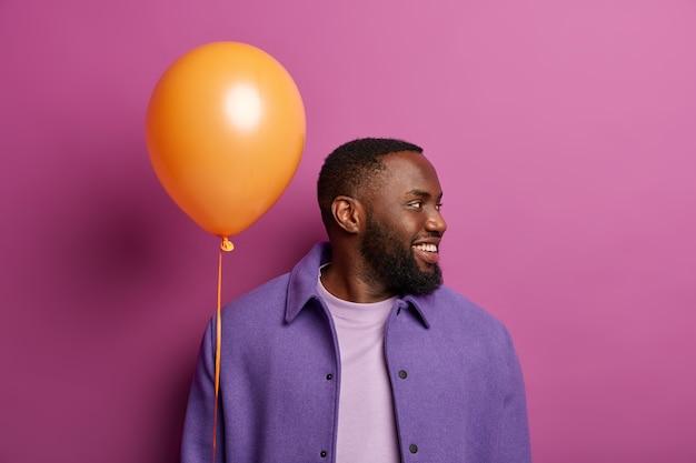 Foto van een gelukkige bebaarde man wendt zich af, ziet iemand aan de rechterkant, wacht vriendin met ballon in de hand, lacht vriendelijk