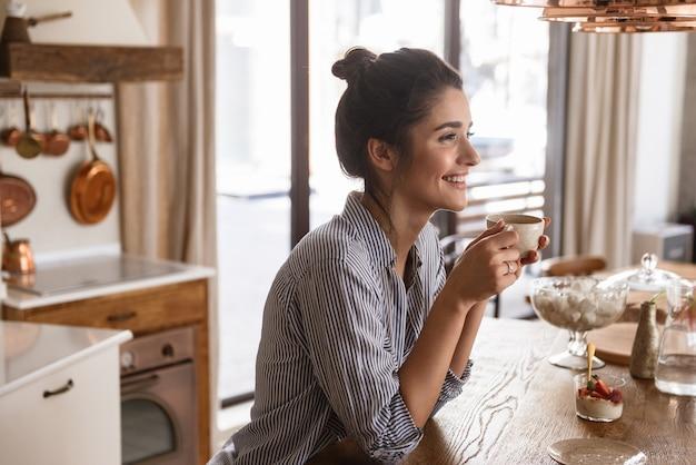 Foto van een gelukkige brunette vrouw die koffie drinkt tijdens het ontbijt in een stijlvolle keuken thuis