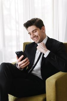 Foto van een gelukkige brunette zakenman die een zwart pak draagt en een videogesprek voert op de mobiele telefoon terwijl hij op een fauteuil in een hotelappartement zit