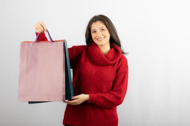 Foto van een gelukkige dame die haar kleurrijke boodschappentassen laat zien.