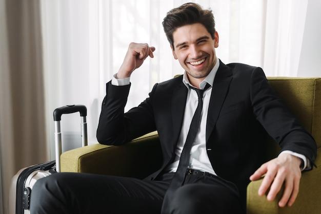 Foto van een gelukkige europese zakenman die een zwart pak draagt dat op een fauteuil zit met een koffer in een hotelappartement
