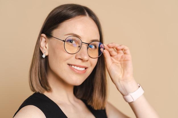 Foto van een gelukkige jonge blanke zakenvrouw met een bril die over een beige muur staat