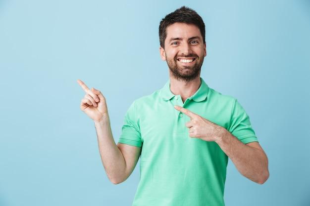 Foto van een gelukkige jonge knappe bebaarde man die zich voordeed over een blauwe muur wijzend.