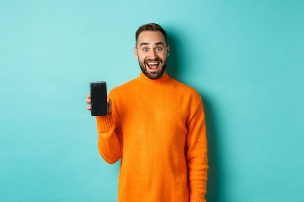 Foto van een gelukkige man die mobiel scherm toont, online winkel, applicatie introduceert, staande over turkooizen muur.
