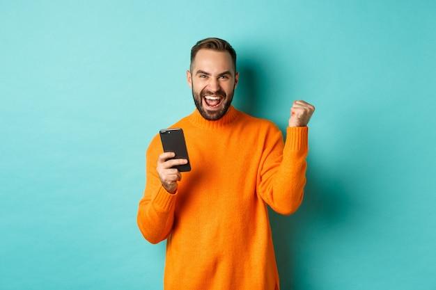 Foto van een gelukkige man die zegeviert, een mobiele telefoon vasthoudt en een winnaargebaar maakt, zich verheugt en een doel bereikt, staande over een lichtblauwe achtergrond.