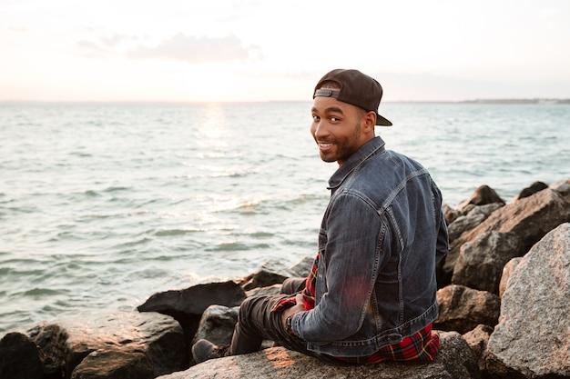 Foto van een gelukkige man met een pet die op het strand loopt. camera kijken.