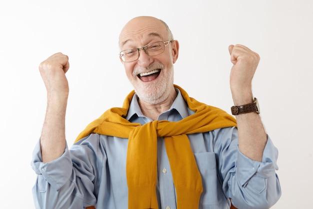 Foto van een gelukkige volwassen man die zich dolblij en opgewonden voelt nadat hij in de loterij heeft gewonnen, opgewekt uitroepend, met gebalde vuisten. mensen, geluk, succes, opwinding, winnen, overwinning en geluk