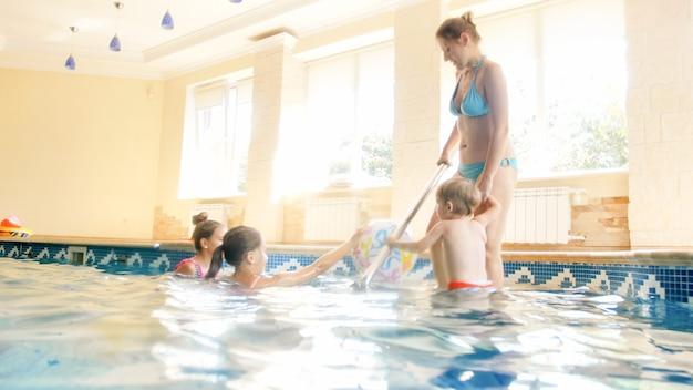 Foto van een gelukkige vrolijke familie die plezier heeft in het zwembad. jonge moeder met drie kinderen in sportschool met zwembad swimming