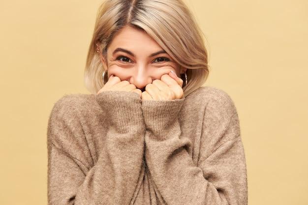 Foto van een gelukkige, vrolijke jonge europese vrouw kan haar extatische emoties niet verbergen, in een goed humeur, overweldigd door positief geweldig nieuws, mond achter handen verbergen, warme trui met lange mouwen dragen