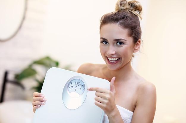Foto van een gelukkige vrouw met een weegschaal in de badkamer