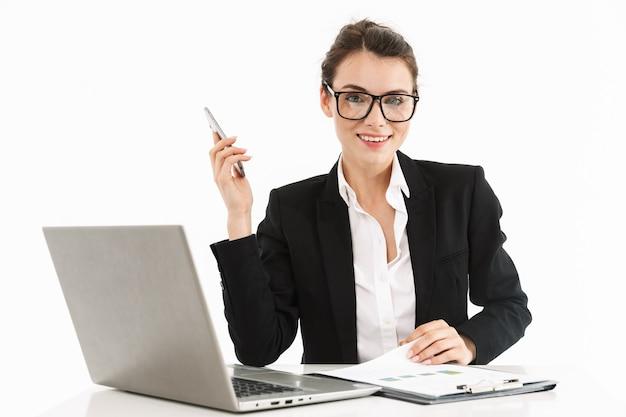 Foto van een gelukkige werkneemster, gekleed in formele kleding, zittend aan een bureau en werkend op een laptop op kantoor geïsoleerd over een witte muur