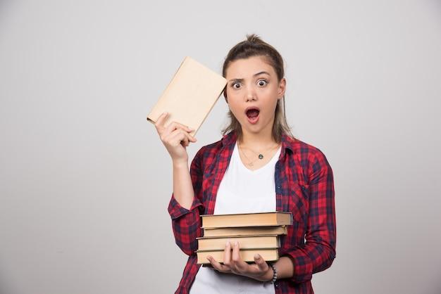Foto van een geschokte student die een stapel boeken vasthoudt.