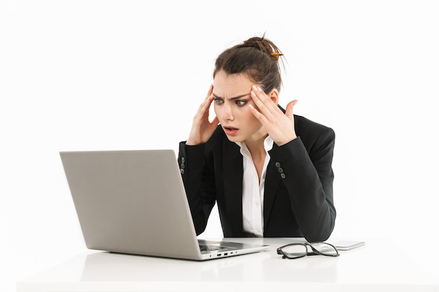 Foto van een gespannen werkneemster, gekleed in formele kleding, zittend aan een bureau en werkend op een laptop op kantoor geïsoleerd over een witte muur