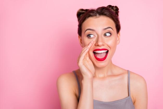 Foto van een geweldig jong meisje grappige broodjes rode lippen houden palm in de buurt van mond gek babbeltje sluw het delen van verse roddels menigte dragen casual grijze tanktop geïsoleerde roze kleur