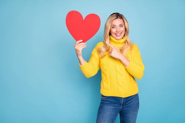Foto van een geweldige blonde dame met een grote rode papieren hartdatumuitnodiging met vermelding van vinger opgewonden slijtage gebreide gele trui jeans geïsoleerde blauwe kleur muur