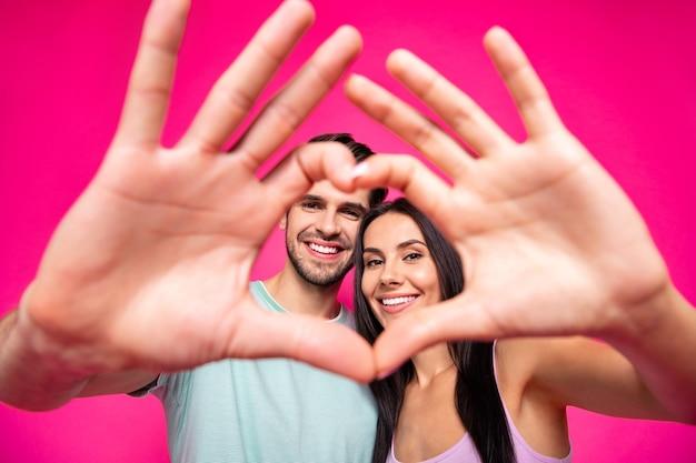 Foto van een geweldige man en dame die een hartfiguur maken met de armen gelegen gezichten erin, dragen casual outfit geïsoleerde roze kleur achtergrond