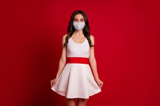 Foto van een geweldige mooie schattige dame die een golvende rok vasthoudt, een goed humeur, een flirterige persoon, een medisch covid-masker, een witte korte jurk, een geïsoleerde rode achtergrondkleur draagt