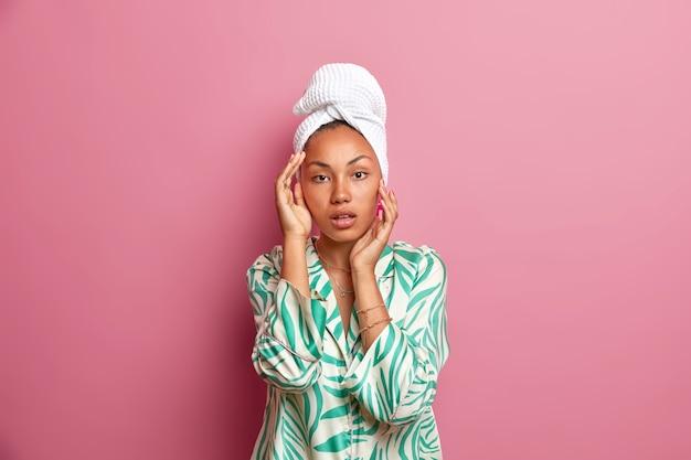 Foto van een gezonde serieuze etnische vrouw heeft een gladde, frisse huid na het douchen, raakt het gezicht zachtjes aan en draagt een casual nachtkleding gewikkelde badhanddoek op het hoofd. natuurlijke schoonheid