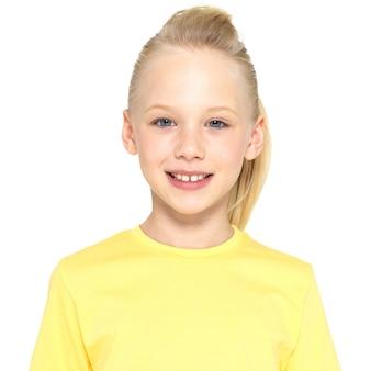 Foto van een glimlachend jong gelukkig meisje dat camera bekijkt die op witte achtergrond wordt geïsoleerd