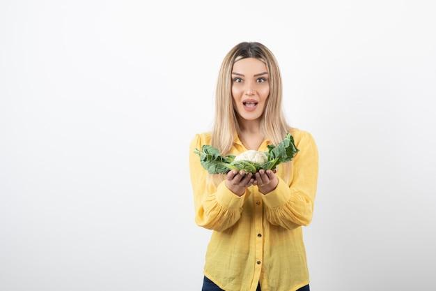 Foto van een glimlachend mooi vrouwenmodel dat en bloemkool houdt.