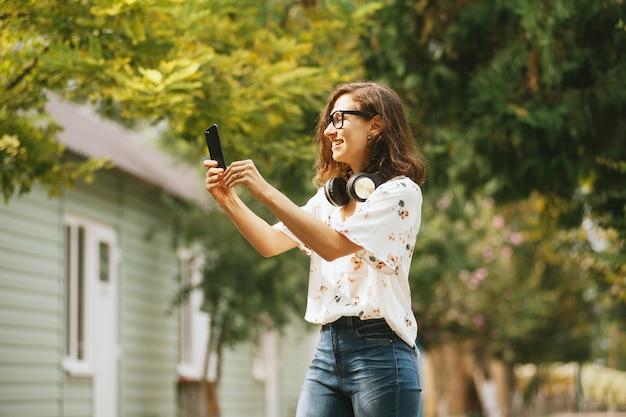 Foto van een glimlachende jonge vrouw die een selfiefoto buiten neemt
