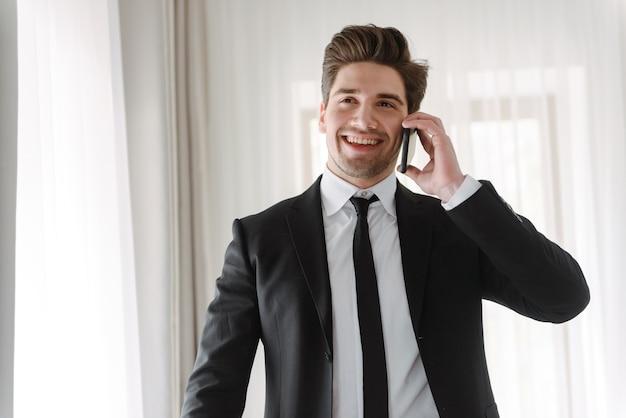 Foto van een glimlachende knappe zakenman die een zwart pak draagt en op een mobiele telefoon praat in een hotelappartement