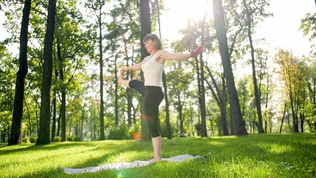Foto van een glimlachende vrouw van middelbare leeftijd die yoga asana beoefent. persoon mediteren in de natuur. balans en harmonie van lichaam en geest Premium Foto